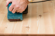 Mans hand on belt sander on pine wood