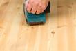 Mans hand on belt sander on pine wood