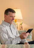 Senior man reading eBook on couch