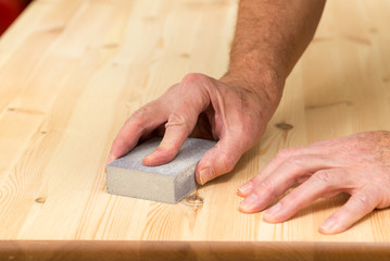 Mans hand on sanding block on pine wood
