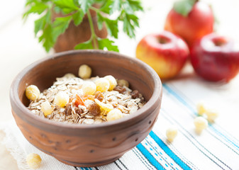 Muesli in a ceramic bowl and fresh apples in the background