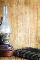 Vintage kerosene lamp and book on table over wooden background