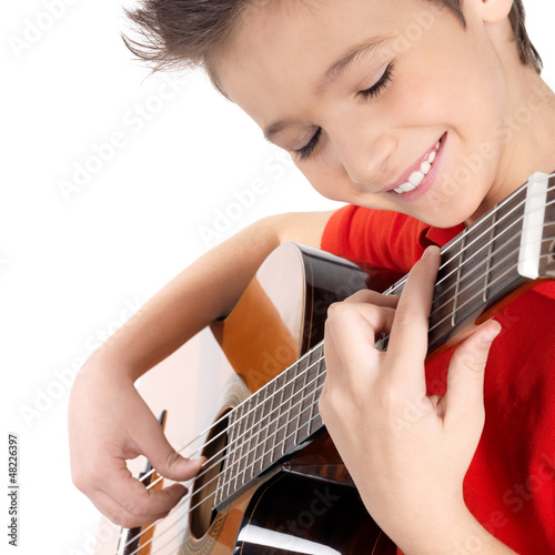Smiling boy is playing on acoustic guitar