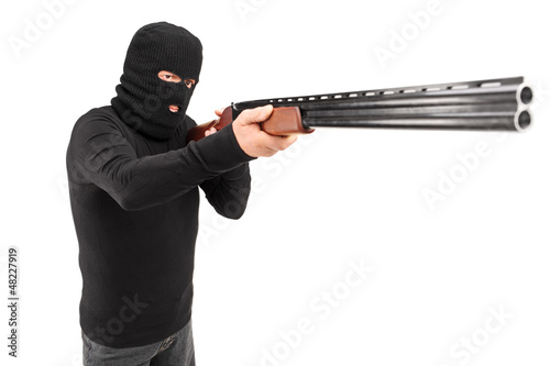 A man with robbery mask attacking someone with shotgun