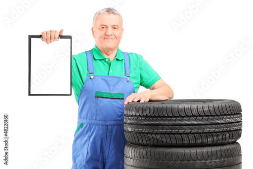 A mature worker on car tyres holding a clipboard