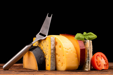 Various types of cheese and knife isolated on black