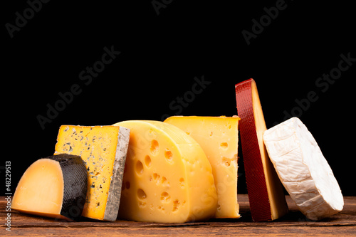 Various types of cheese on wooden table and black background