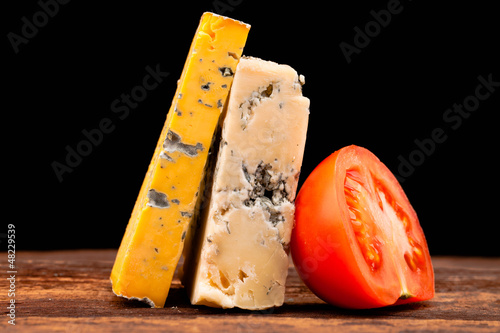 Various types of cheese and tomatoes isolated on black