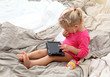 Toddler girl playing with a tablet pc in bed