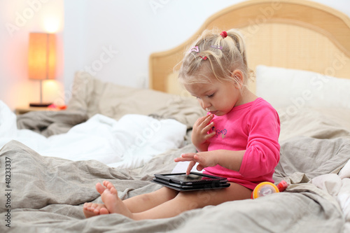 Toddler girl playing with tablet pc in bed