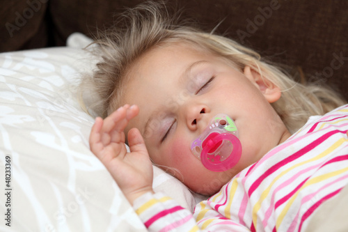 Toddler girl sleeping in bed
