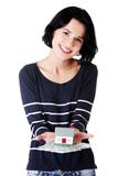 Woman holding polish zloty bills and house model