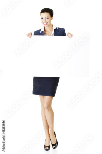 Smiling business woman showing blank signboard