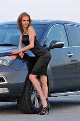 Fashion model posing pretty in front of sport SUV in New York NY