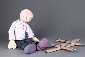 Wooden puppet sitting on grey background