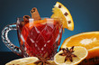 Fragrant mulled wine in glass with spices and oranges around
