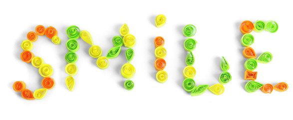 The word smile is made of quilling isolated on white