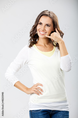 Young woman showing call me gesture, on gray