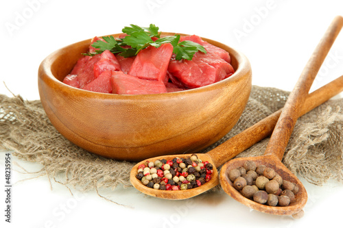 Raw beef meat in bowl with herbs and spices isolated on white