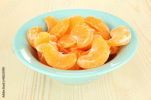 Tasty mandarine's slices in color bowl on light background