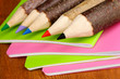 Colorful wooden pencils with exercisebooks on wooden table