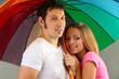 Loving couple with umbrella on grey background