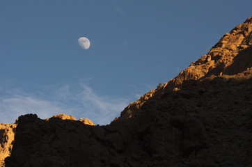 small moon over a mountain cliff in the desert