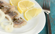 Dish of herring on plate on blue wooden table close-up