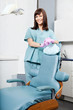 Smiling Female Dentist Standing By Dental Chair At Clinic