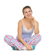 Thoughtful young woman in pajamas sitting on floor