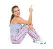 Smiling young woman in pajamas sitting on floor