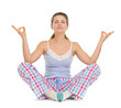 Happy young woman in pajamas sitting on floor and meditating