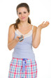 Bored young woman in pajamas holding TV remote control