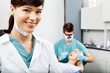 Female Hygienist With Dentist Working In The Background