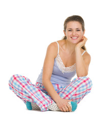 Young woman in pajamas sitting on floor isolated on white
