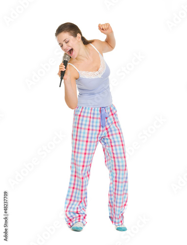 Full length portrait of woman in pajamas singing in microphone