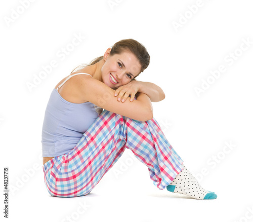 Happy young woman in pajamas sitting on floor