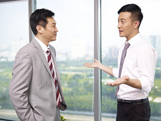 asian business people standing and talking in office