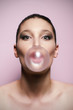 Woman blowing a big bubble gum bubble