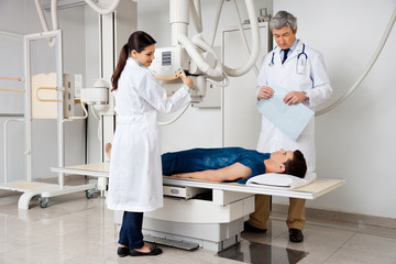 Radiologists With Patient In X-ray Room