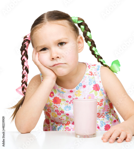 Gloomy little girl doesn't want to drink milk