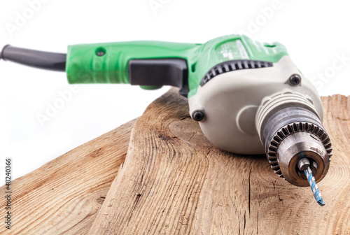 The electric drill, on old wooden boards
