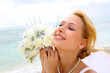 Portrait of beautiful bride with eyes shut by the beach