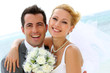 Leinwanddruck Bild - Cheerful married couple standing on the beach