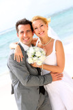 Fototapety Cheerful married couple standing on the beach
