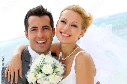 Leinwanddruck Bild Cheerful married couple standing on the beach
