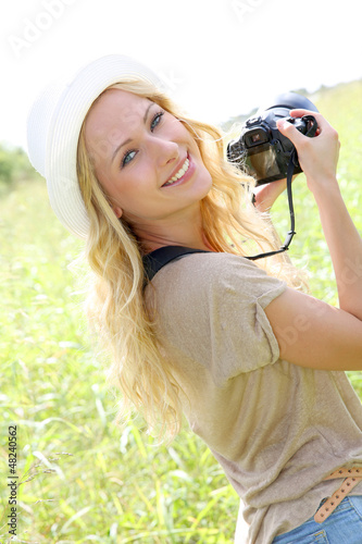 Portrait of adventure girl using photo camera in nature