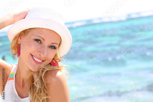 Beautiful girl wearing hat at the beach