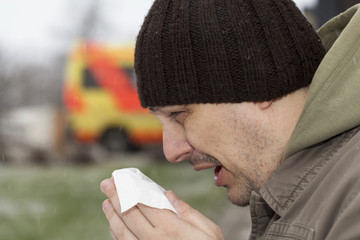 Man with a runny nose and  napkin in hands near hospital