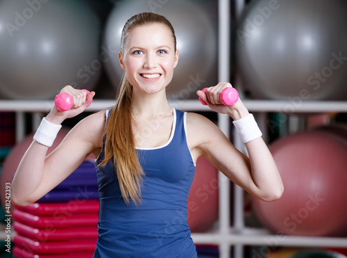 Beautiful athlete woman in sportswear working out with dumbbells